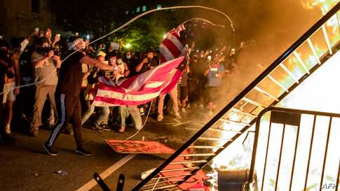 Protesters throw a US flag into a fire during a demonstration outside the White House over the death of George Floyd at the…