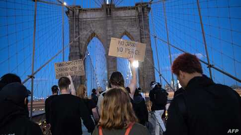 NEW YORK, NEW YORK - MAY 31: Protesters walk over the Brooklyn Bridge during a march to honor George Floyd in Manhattan on May…