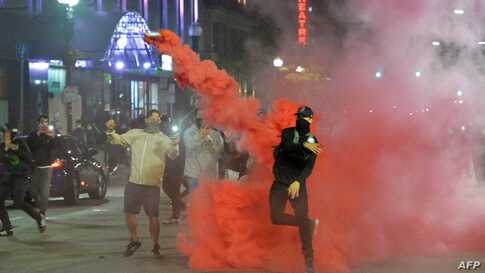 Protesters throw back smoke canisters during clashes with police during a demonstration over the death of George Floyd, an…