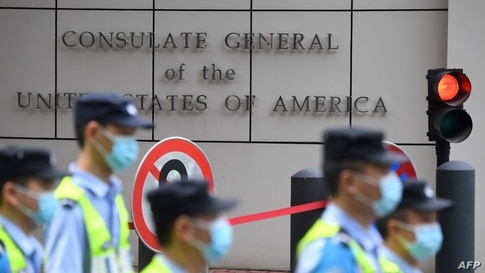 Policemen walk past the US consulate in Chengdu, southwestern China's Sichuan province, on July 26, 2020. - Tensions have…