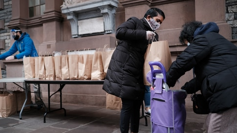 NEW YORK, NEW YORK - DECEMBER 02: People receive bags of food at a lower Manhattan church that holds a weekly food distribution…