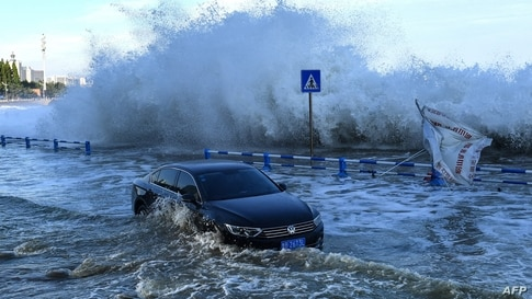 This photo taken on July 25, 2021 shows a car sitting in flood waters as waves, caused by Typhoon In-Fa further down the…