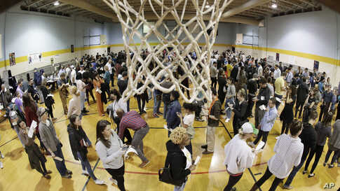 People wait to vote on Super Tuesday in the gymnasium at Cleveland Park Community Center, Tuesday, March 3, 2020, in Nashville,…