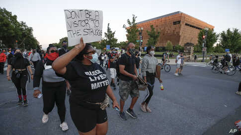 Demonstrators walk past the Smithsonian National Museum of African American History and Culture at they protest the death of…
