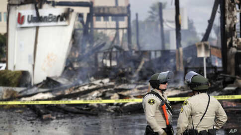 San Diego County sheriff officers stand guard in front of a burning bank building after a protest over the death of George…