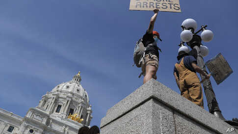 A demonstrator protests outside the state capitol, Sunday, May 31, 2020, in Minneapolis. Protests continued following the death…