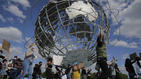 Protesters march around a large sculpture of a globe in Flushing Meadows Corona Park in the Queens borough of New York, Sunday,…