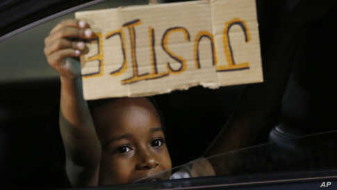 "A young boy holds a ""Justice"" sign as he peers outside the window of a car passing protesters marching through downtown for a…"