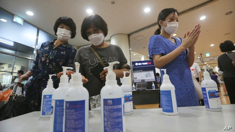 Christians wearing face masks to help protect against the spread of the new coronavirus use hand sanitizer before attending a…