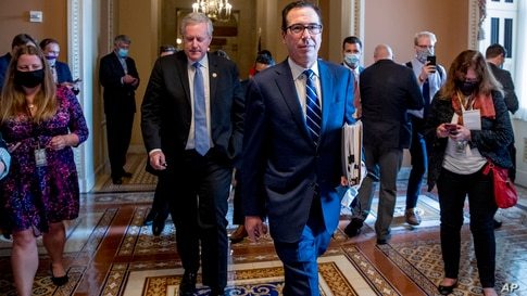 Treasury Secretary Steven Mnuchin, right, accompanied by White House chief of staff Mark Meadows, left, leave a meeting with…