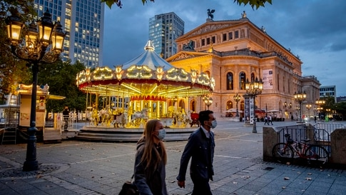 People wearing face masks walk past a carousel and the Old Opera in Frankfurt, Germany, Wednesday, Oct. 28, 2020. To avoid the…