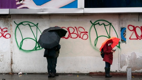 People under umbrellas practice social distancing as they line up for early voting, Friday, Oct. 30, 2020, in the Brooklyn…
