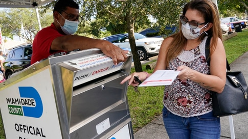 Carlos Amado, left, with the Miami-Dade Supervisor of Elections, guides Isabel Lui to the slot to drop off her ballot, Friday,…