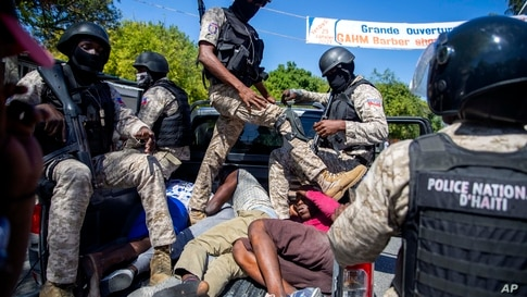 Police move detained demonstrators in the bed of a pick-up truck to a police station during a protest to demand the resignation…