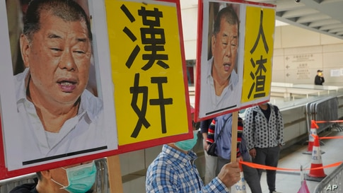 Pro-China supporters hold the pictures of prominent Hong Kong democracy advocate and newspaper founder Jimmy Lai with Chinese…