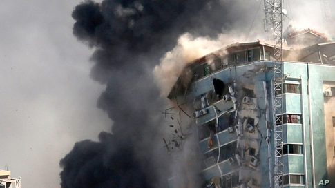The building housing the offices of The Associated Press and other media in Gaza City collapses after it was hit by an Israeli…