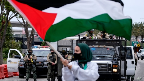 A demonstrator waves the flag of Palestine as police officers guard outside the Federal Building during a protest against…