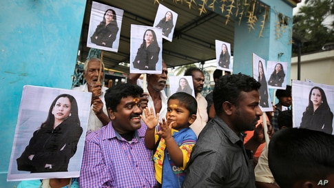 Villagers hold placards featuring US Vice President-elect Kamala Harris outside a Hindu temple in Thulasendrapuram, the hometown of Harris' maternal grandfather, south of Chennai, Tamil Nadu state, India, Jan. 20, 2021.