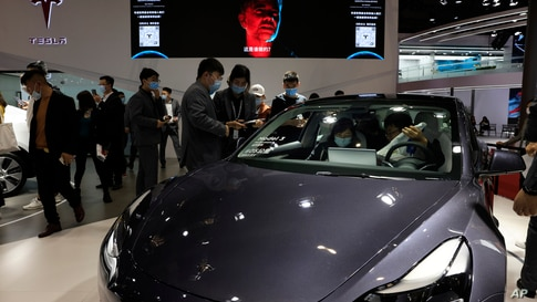 Visitors look at a Tesla Model 3 during the Shanghai Auto Show in Shanghai, April 21, 2021.