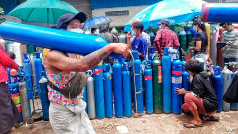 A man carries an oxygen tank as he walks past people waiting with oxygen tanks in need of refill outside the Naing oxygen…