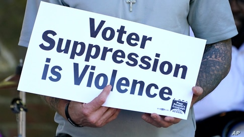 Benny Ivey, a former felon, holds a sign addressing voter suppression during a Poor People's Campaign assembly in downtown…