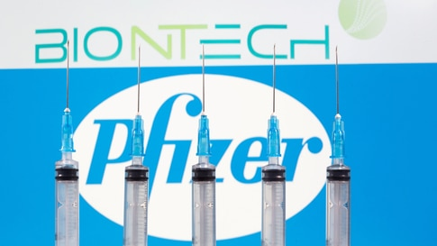 FILE PHOTO: Syringes are seen in front of displayed Biontech and Pfizer logos in this illustration