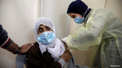 FILE PHOTO: A Palestinian health worker gives a woman a dose of AstraZeneca vaccine against the coronavirus disease (COVID-19) during a vaccination drive in Tubas, in the Israeli-occupied West Bank