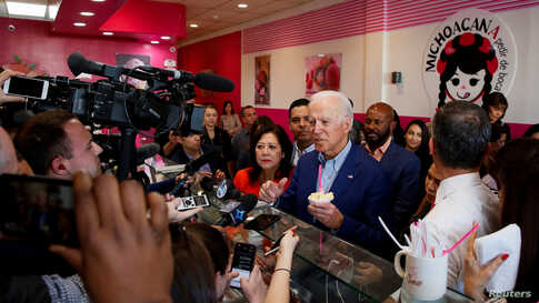 Democratic U.S. presidential candidate and former U.S. Vice President Joe Biden talks to reporters after ordering ice-cream at…