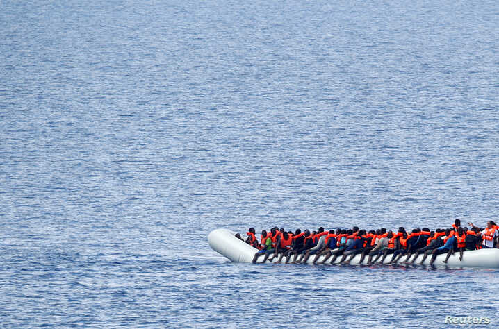 """Migrants wait to be rescued by """"Save the Children"""" NGO crew from the ship Vos Hestia in the Mediterranean sea off Libya coast, June 18, 2017."""