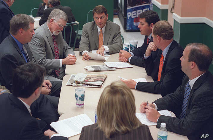 FILE - Lobbyist Brian Ballard, center meets with other lobbyists, from center to left, Mac Stipanovich, Gene McGee Joe McCann, Courtney Bense, Greg Turbeville, Matt Bryan, and Clark Smith in the Capitol cafeteria before the legislative session begins