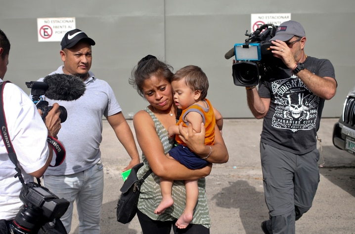 Adalicia Montecino and her husband Rolando Bueso Castillo are surrounded by the media as they walk with their year-old son Johan Bueso Montecinos, who became a poster child for the U.S. policy of separating immigrants and their children, in San Pedro