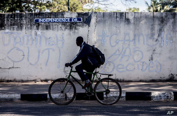 A man rides his bicycle past graffiti on a wall in Banjul, Gambia, Jan. 24, 2017.