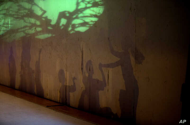 Dancers' shadows are cast on a stage backdrop during the contemporary dance production Ubuntu, at the Teresa Carreno Theater in Caracas, Venezuela, Dec. 4, 2018.