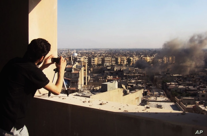In this citizen journalism image provided by Shaam News Network, a Syrian citizen journalist documents Syrian forces shelling in Homs, Syria, July 24, 2012.