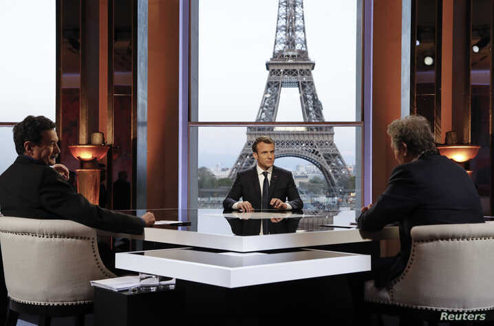 French President Emmanuel Macron (C) poses on the TV set before an interview with BFM journalist Jean-Jacques Bourdin (R) and Mediapart investigative website journalist Edwy Plenel (L), at the Theatre National de Chaillot across from the Eiffel Tower...
