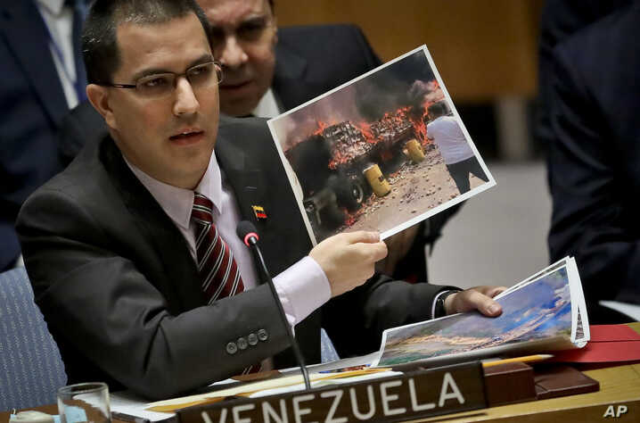 Venezuela Foreign Affairs Minister Jorge Arreaza shows pictures he said represent opposition members initiating violence during a meeting on Venezuela in the U.N. Security Council at U.N. headquarters, Tuesday Feb. 26, 2019.