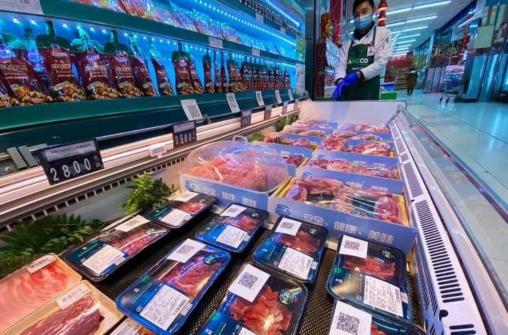 A worker wearing a mask and gloves stand near beef products from New Zealand packaged with a QR-code linked to its coronavirus…