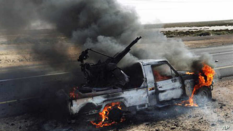 A pro-Moammar Gadhafi anti-aircraft machine gun is burned by Libyan rebels during a battle, in the town of Brega, east of Libya, March 2, 2011
