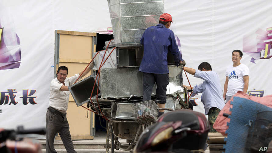 FILE - Workers remove air ducts made from aluminum sheet metal in Beijing, China, Aug. 22, 2016. On Thursday, the U.S. filed a complaint against China for allegedly giving its aluminum industry an unfair advantage by providing it with cheap loans and
