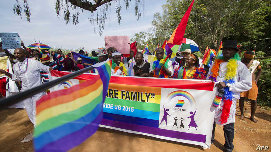 People holding rainbow flags take part in the Gay Pride parade in Entebbe, Aug. 8, 2015.