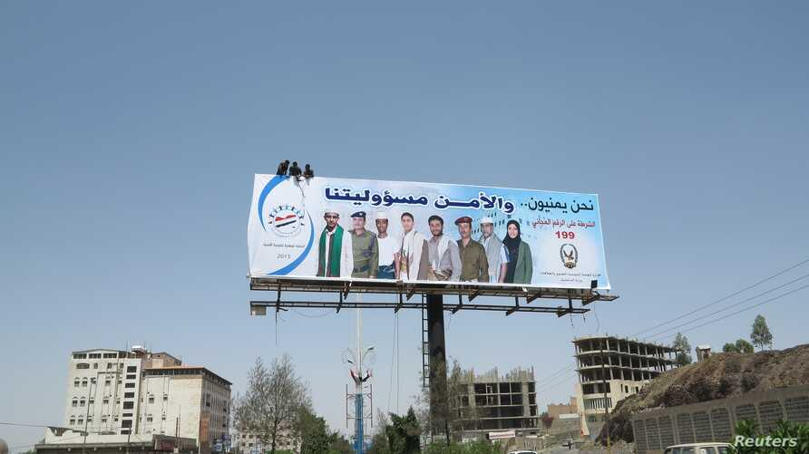 Workers put up a billboard urging citizens to cooperate with security authorities in Sana'a, Yemen, September 30, 2013, the day of the suspected al-Qaida militant attack on an army base in the eastern city of al-Mukalla.