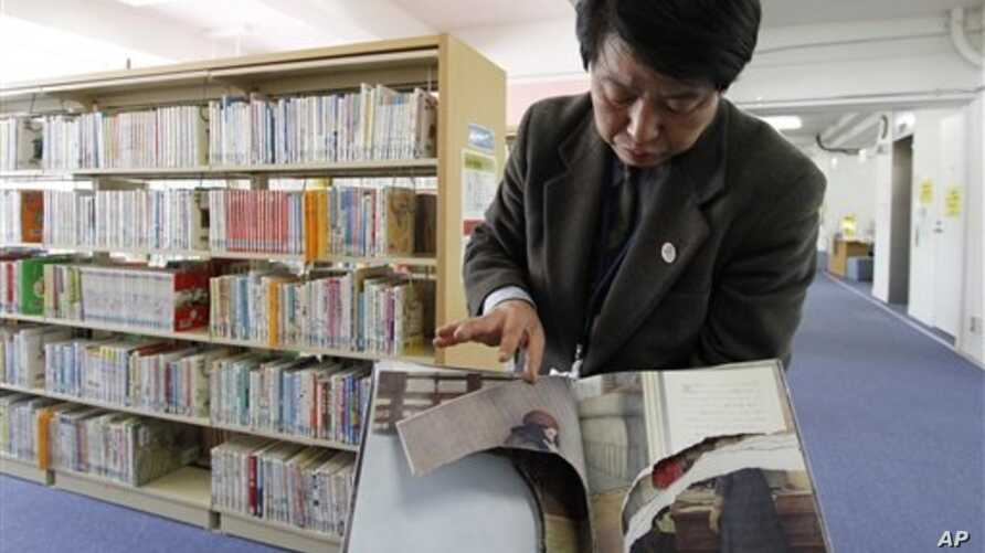 """A ripped copy of Anne Frank's """"Diary of a Young Girl"""" picture book is shown by Shinjuku City Library Director Kotaro Fujimaki at the library in Tokyo Friday, Feb. 21, 2014. Tokyo Libraries said on Friday that hundreds of copies of Anne Frank's diary"""