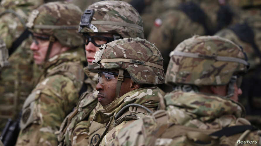 FILE - U.S. soldiers attend a welcoming ceremony for U.S.-led NATO troops at a military training site near Orzysz, Poland, April 13, 2017.