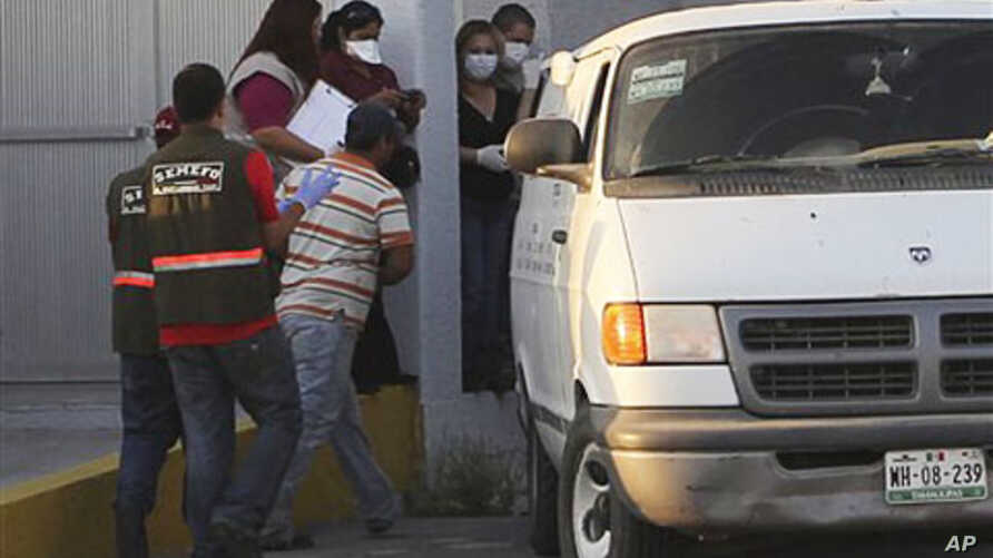 Forensic workers prepare to transfer bodies from a van into a large truck, not seen, in the northern border city of Matamoros, Mexico, April, 6, 2011