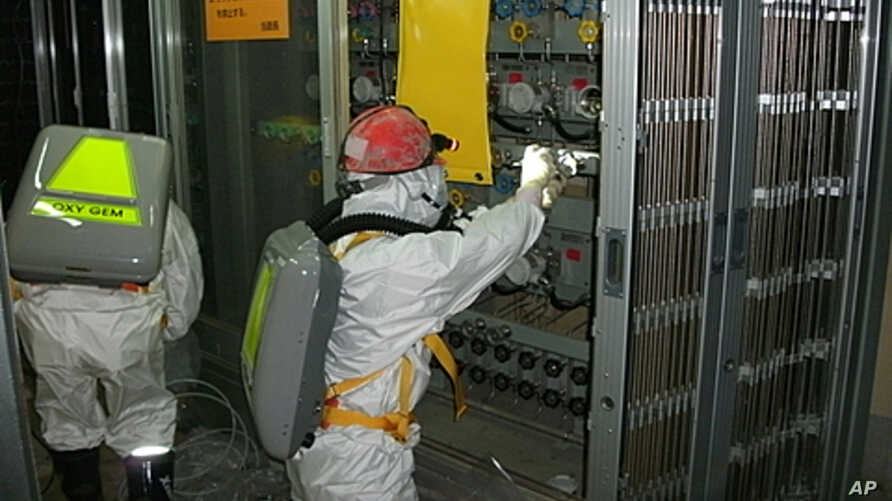 Workers wearing protective suits check the status of the water level indicator at the fuel area inside reactor number 1 at the crippled Fukushima-Daiichi Nuclear Power Plant in this handout photo released by TEPCO May 12, 2011