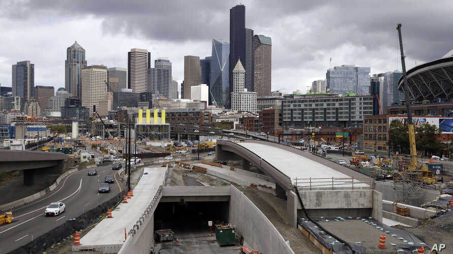 A portion of a new offramp, center right, for Highway 99, stands completed and adjacent to the entrance for northbound traffic into the tunnel being constructed in Seattle. The offramp has a new type of column that flexes when the ground shakes in an