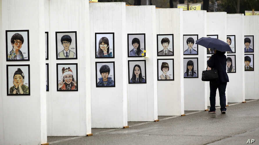 A woman looks at caricatures of the victims of the sunken ferry Sewol outside a group memorial altar in Ansan, South Korea, Thursday, April 16, 2015.