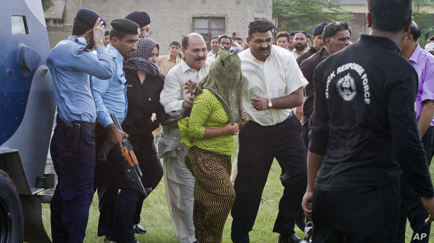 Pakistani police officials escort a young Christian girl accused of blasphemy for allegedly burning pages of a Quran, toward a helicopter following her release from central prison on the outskirts of Rawalpindi, September 8, 2012.