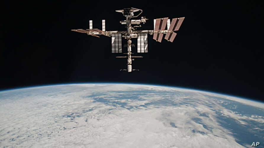 This May 23, 2011 photo released by NASA shows the International Space Station above the Earth, taken by Expedition 27 crew member Paolo Nespoli from the Soyuz TMA-20 following its undocking.
