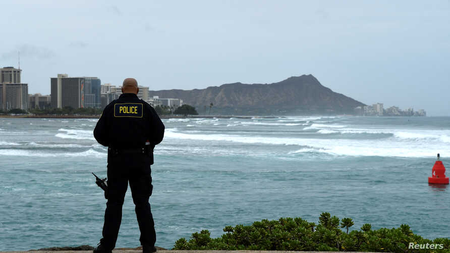 Honolulu police officer Chad Asuncion monitors the water conditions and warns surfers about the conditions as Hurricane Lane approaches Honolulu, Hawaii, Aug. 23, 2018.
